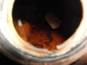The inside of a fuel tank showing heavy contamination with rust and sludge
